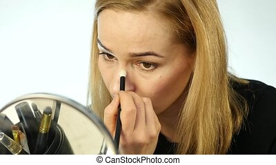 Beautiful woman doing everyday makeup and holding makeup brush in front of mirror. slow motion