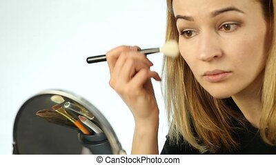 Beautiful woman doing everyday makeup and holding makeup...