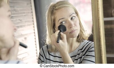 Beautiful woman doing everyday makeup and holding makeup brush in front of mirror