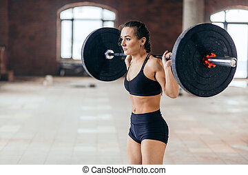 beautiful woman doing exercise with barbell load on back