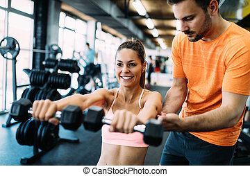 Beautiful woman doing exercises in gym with personal trainer