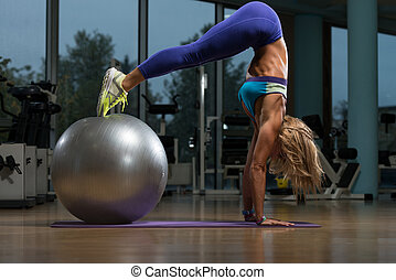 Beautiful Woman Doing Pike Up With Stability Ball - Middle...