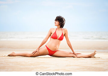 Beautiful woman doing yoga exercise on the beach