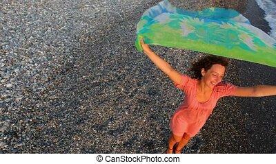 beautiful woman dressed in bikini with fabric standing on beach, flying camera