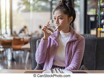 woman drinking a glass of water in restaurant
