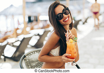 Beautiful woman drinking cocktail in summer