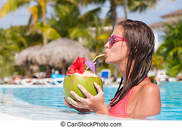 beautiful woman drinking coconut by the pool