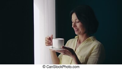 Beautiful woman drinking coffee and looking out of window