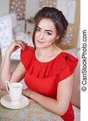 Beautiful woman drinking coffee in the kitchen