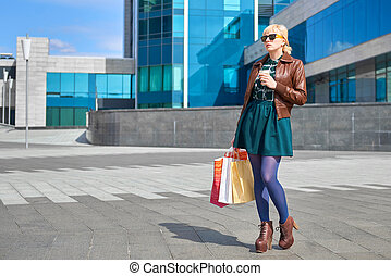 Beautiful woman drinking coffee with shopping bags