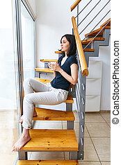 Beautiful woman drinking hot coffee sitting on stairs at home