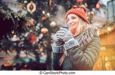 Beautiful woman drinking mulled wine on Christmas market