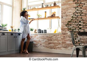 Beautiful woman drinking orange juice in the kitchen.