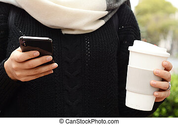Beautiful woman drinking paper cup of coffee and using a her phone