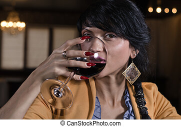 Beautiful woman drinking red wine in a bar