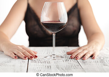 Beautiful woman drinking red wine siting on a sofa