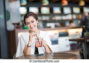 Beautiful woman drinking sweet drink in Cafe