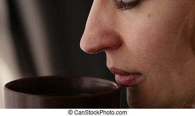 beautiful woman drinks coffee or tea looking out the window. slow motion