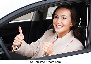 Beautiful woman driver smiling and giving thumb up inside her car