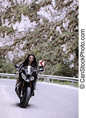 Beautiful woman driving a motorcycle on a mountain road