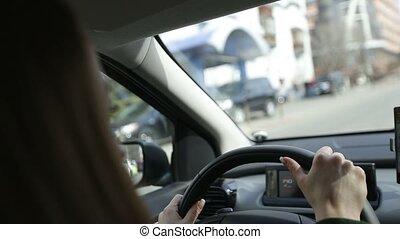 Beautiful woman driving car through modern city