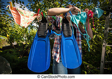 woman drying flippers and snorkeling mask on clothesline