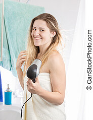 Beautiful woman drying hair in bathroom at home