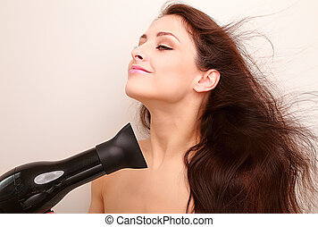 Beautiful woman drying long healthy hair with natural joying emotion