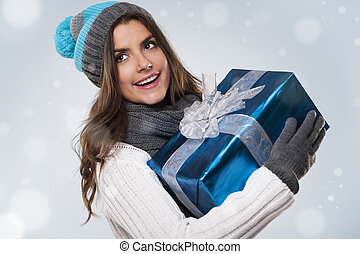 Beautiful woman during the magic christmas time with blue gift
