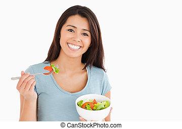 Beautiful woman eating a bowl of salad