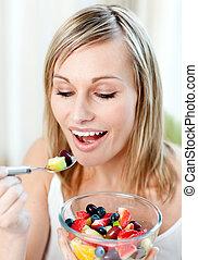 Beautiful woman eating a fruit salad