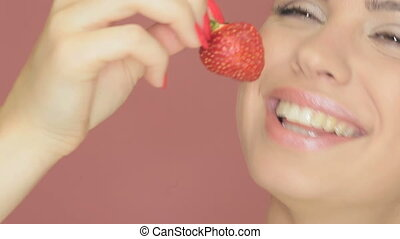 Beautiful woman eating a strawberry