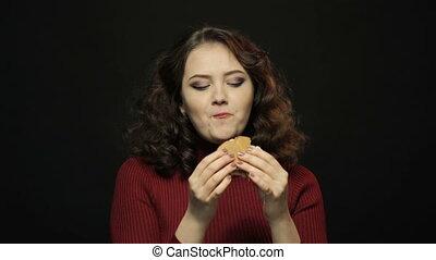 Beautiful woman eating burger, closeup shooting
