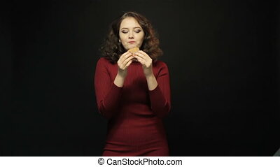 Beautiful woman eating burger on black background