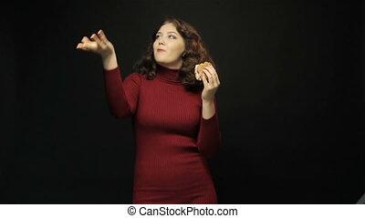 Beautiful woman eating cheeseburger on black background