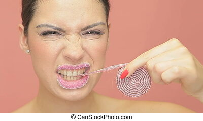 Beautiful woman eating coiled jelly - Beautiful woman with...