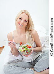 Beautiful woman eating green salad