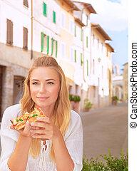 Beautiful woman eating pizza