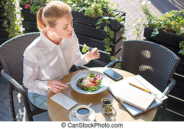 Beautiful woman eating salad on restaurant terrace