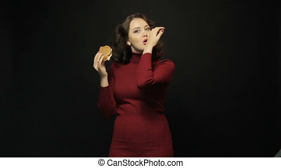 Beautiful woman eating sandwich on black background