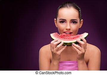 Beautiful woman eating tasty watermelon