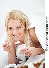 Beautiful woman eating yogurt in bed
