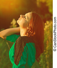 Beautiful woman enjoy sunshine in summer day on yellow background. Girl looking up with closed eyes