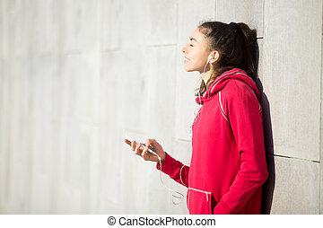 Beautiful woman enjoying music in her phone player