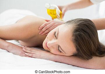 Beautiful woman enjoying oil massage at beauty spa - Close...