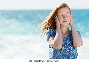 Beautiful woman enjoying the sea breeze