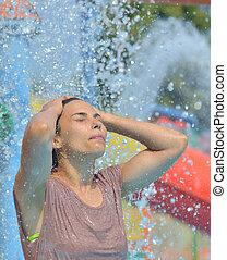 Beautiful woman enjoying under a water jet with thousands of drops in the background