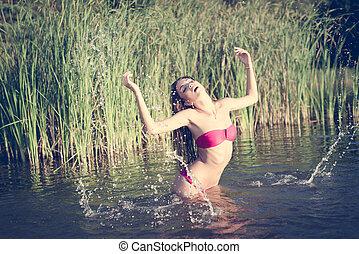 Beautiful woman enjoying water: beauty model girl having fun splashing water on green summer outdoors copy space background