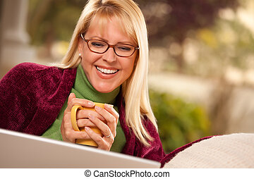 Beautiful Woman Enjoys Her Warm Drink and Laptop