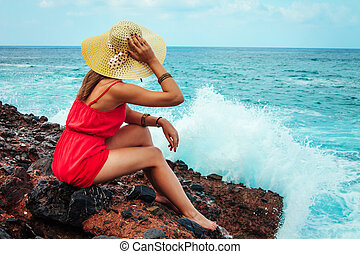 Beautiful woman enjoys the view of waves on the beach